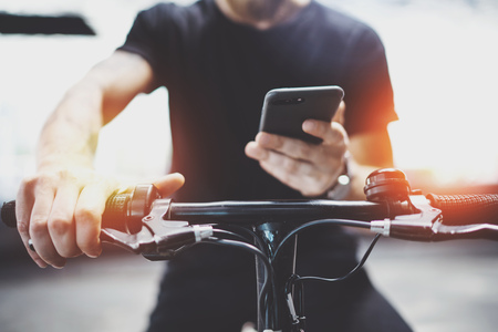 Photo for Tattooed hipster man in holding smartphone hands and using maps app before riding by electric scooter in the city. - Royalty Free Image