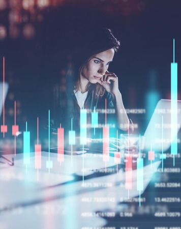 Foto de Young woman working at night modern office loft.Red and green candlestick chart and stock trading on background. Double exposure. - Imagen libre de derechos