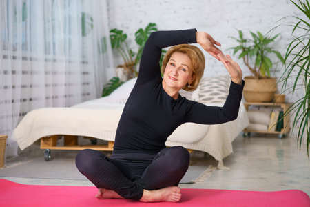 Photo pour Mature woman in a black tracksuit doing yoga sitting on the Mat at home, against the background of a bed and pots of green plants, healthy lifestyle concept sitting at home - image libre de droit