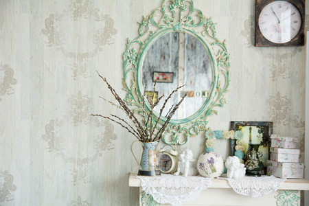 Photo for Vintage interior with mirror and a table with a vase and willows. Designer wall clock. Angels on the table - Royalty Free Image