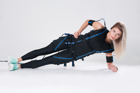 Foto de Blonde in an electric muscular suit for stimulation makes an exercise on the rug. Young woman in EMC suit isolated on white background - Imagen libre de derechos