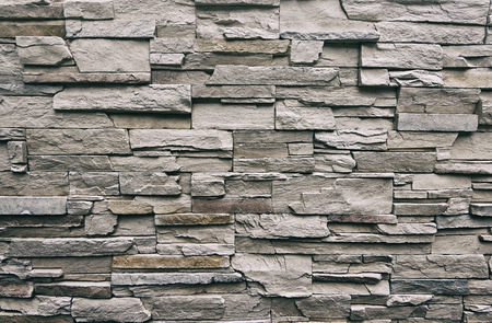 Foto de Close up of modern style design decorative uneven cracked real stone wall surface with cement, old vintage - Imagen libre de derechos