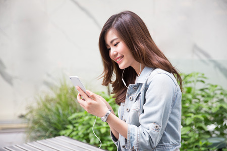 Photo pour Young asian girl playing mobile phone - image libre de droit