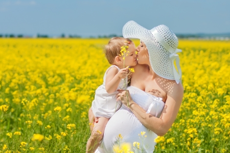 Pregnant mother and her daughter have fun outdoor