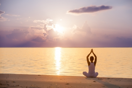 Photo for Caucasian woman practicing yoga at seashore - Royalty Free Image