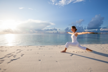 Photo pour Caucasian woman practicing yoga at seashore - image libre de droit