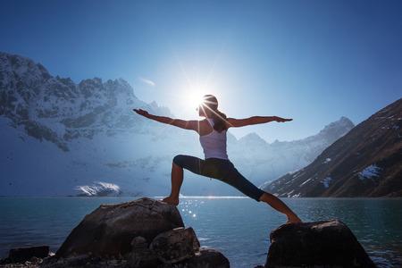Foto de Young woman is practicing yoga at mountain lake - Imagen libre de derechos