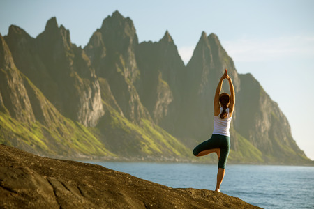 Foto de Young woman is practicing yoga between mountains in Norway - Imagen libre de derechos