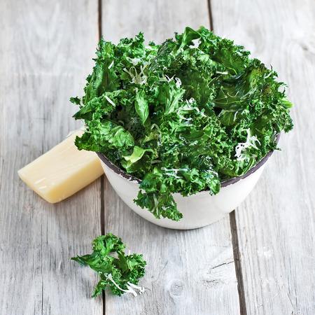 Photo pour Kale chips with parmigano cheese in ceramic bowl. Selective focus. - image libre de droit