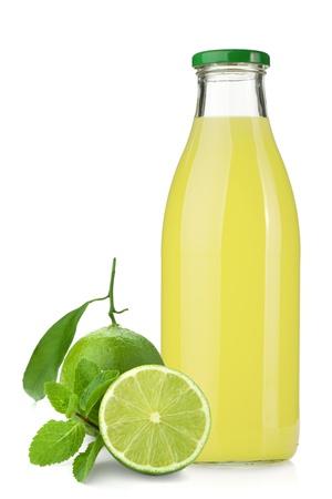 Foto de Lemon juice glass bottle, ripe limes and mint. Isolated on white background - Imagen libre de derechos