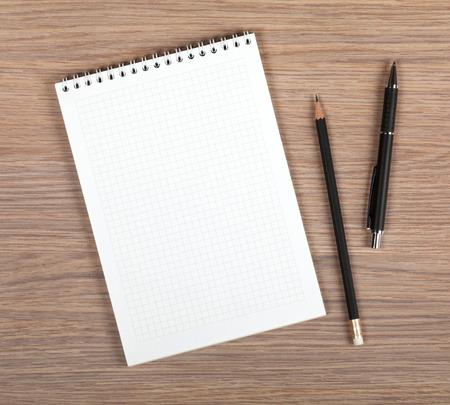 Foto de Blank notepad with pen and pencil on office wooden table - Imagen libre de derechos