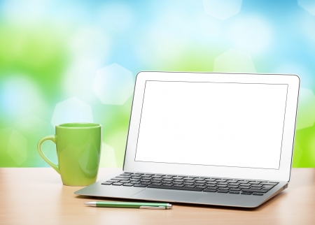 Photo for Laptop with blank screen and cup on table over sunny day bokeh background - Royalty Free Image