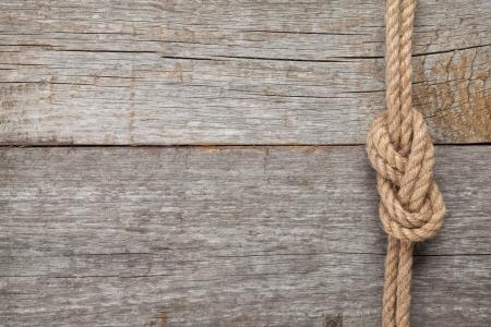 Photo pour Ship rope knot on old wooden texture background - image libre de droit