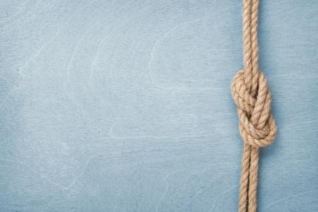 Photo pour Ship rope knot on blue wooden texture background - image libre de droit