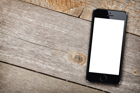 Foto de Smart phone on wooden table background with copy space - Imagen libre de derechos