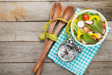 Photo pour Fresh healthy salad and measuring tape on wooden table. Healthy food - image libre de droit
