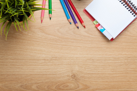 Foto de Office table with flower, blank notepad and colorful pencils. View from above with copy space - Imagen libre de derechos