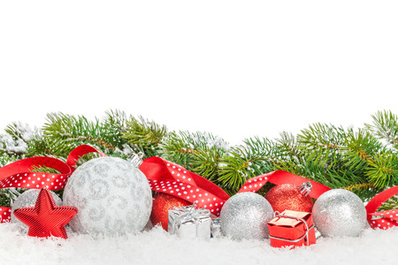 Foto de Christmas baubles and red ribbon with snow fir tree. Isolated on white background with copy space - Imagen libre de derechos