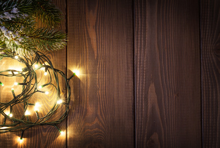 Photo for Christmas lights and snow fir tree over wooden background with copy space - Royalty Free Image