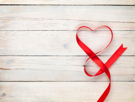 Foto de Valentines day background with heart shaped ribbon over white wooden table background - Imagen libre de derechos