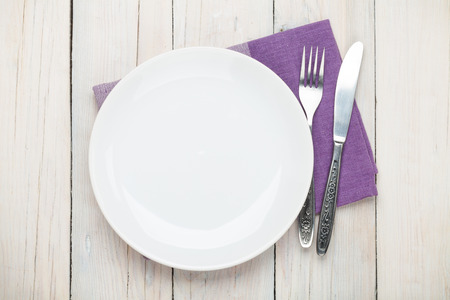 Photo for Empty plate and silverware over white wooden table background. View from above - Royalty Free Image