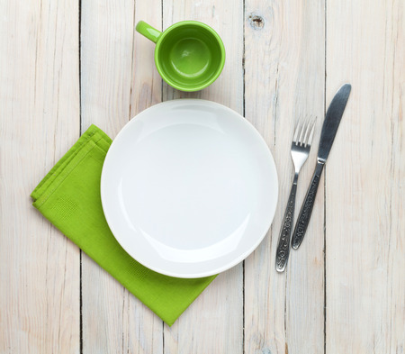 Photo for Empty plate, cup and silverware over white wooden table background. View from above - Royalty Free Image