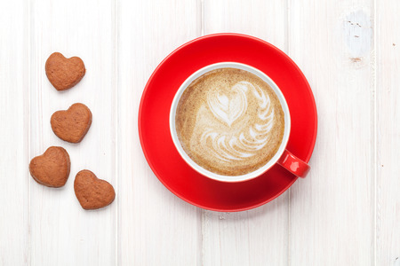 Photo for Valentines day heart shaped cookies and red coffee cup. View from above over white wooden table - Royalty Free Image