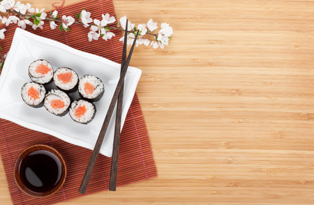 Photo for Sushi maki with salmon and sakura branch over bamboo table - Royalty Free Image