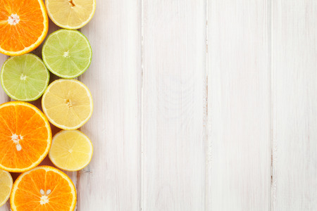 Photo for Citrus fruits. Oranges, limes and lemons. Over wood table background with copy space - Royalty Free Image