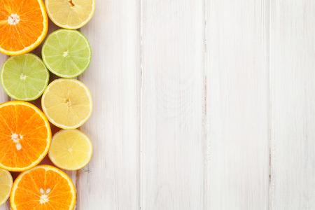 Photo pour Citrus fruits. Oranges, limes and lemons. Over wood table background with copy space - image libre de droit