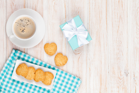 Photo pour Cup of coffee, heart shaped cookies and gift box on white wooden table with copy space - image libre de droit