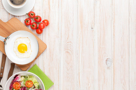 Photo for Healthy breakfast with fried egg, tomatoes and salad on white wooden table with copy space - Royalty Free Image