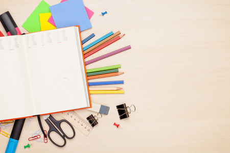 Foto de Blank notepad over school and office supplies on office table. Top view with copy space - Imagen libre de derechos