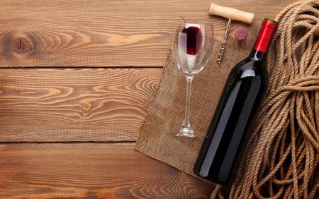Foto de Red wine bottle, wine glass and corkscrew on wooden table background with copy space - Imagen libre de derechos