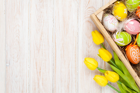 Photo pour Easter background with colorful eggs and yellow tulips over white wood. Top view with copy space - image libre de droit