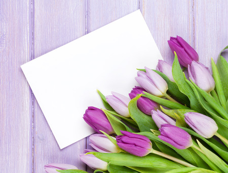 Foto de Purple tulip bouquet and blank greeting card. Top view over wooden table - Imagen libre de derechos