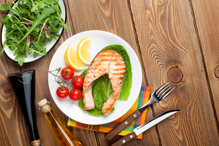 Photo for Grilled salmon, salad and condiments on wooden table. Top view with copy space - Royalty Free Image