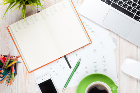 Foto de Office desk table with computer, supplies, coffee cup and flower. Top view with copy space - Imagen libre de derechos
