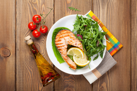 Photo for Grilled salmon, salad and condiments on wooden table. Top view - Royalty Free Image