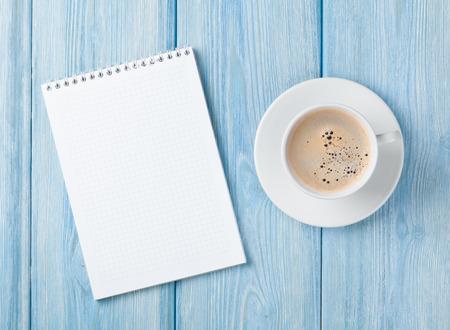 Foto de Coffee cup and blank notepad over blue wooden table. Top view with copy space - Imagen libre de derechos