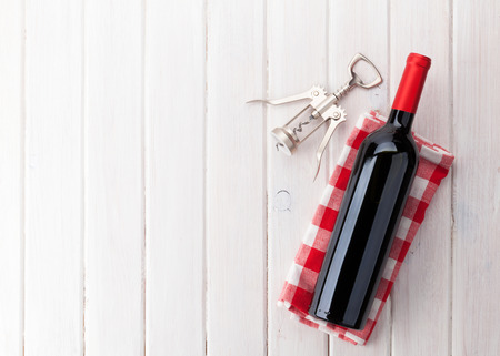 Photo pour Red wine bottle and corkscrew on white wooden table background with copy space - image libre de droit