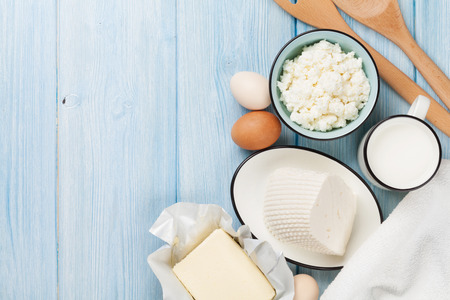 Photo pour Dairy products on wooden table. Milk, cheese, egg, curd cheese and butter. Top view with copy space - image libre de droit