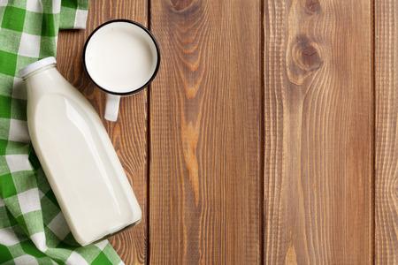 Photo pour Milk cup and bottle on wooden table. Top view with copy space - image libre de droit