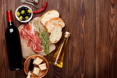 Foto de Prosciutto, wine, olives, parmesan and olive oil on wooden table. Top view with copy space - Imagen libre de derechos