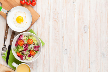 Photo pour Healthy breakfast with fried egg, toasts and salad on white wooden table. Top view with copy space - image libre de droit