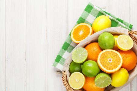 Photo for Citrus fruits in basket. Oranges, limes and lemons. Over white wood table background with copy space - Royalty Free Image