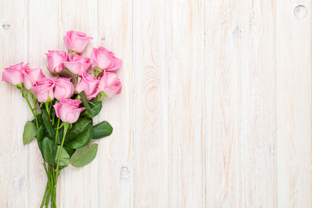 Foto de Pink roses bouquet over wooden table. Top view with copy space - Imagen libre de derechos