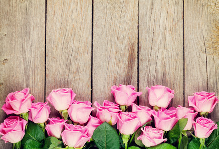 Photo pour Pink roses bouquet over wooden table. Top view with copy space. Toned - image libre de droit