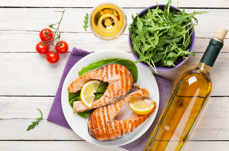 Photo for Grilled salmon and white wine on wooden table. Top view - Royalty Free Image