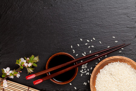 Japanese sushi chopsticks over soy sauce bowl, rice and sakura blossom on black stone background. Top view with copy space
